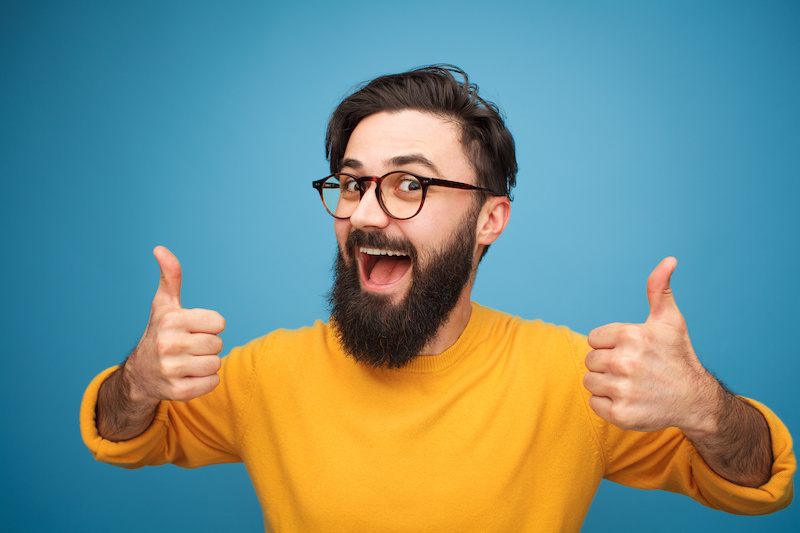 Stylish young hipster with beard wearing eyeglasses and holding thumbs up on blue.