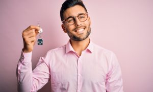 Young real estate business man holding new house keys over pink background with a happy face standing and smiling with a confident smile showing teeth